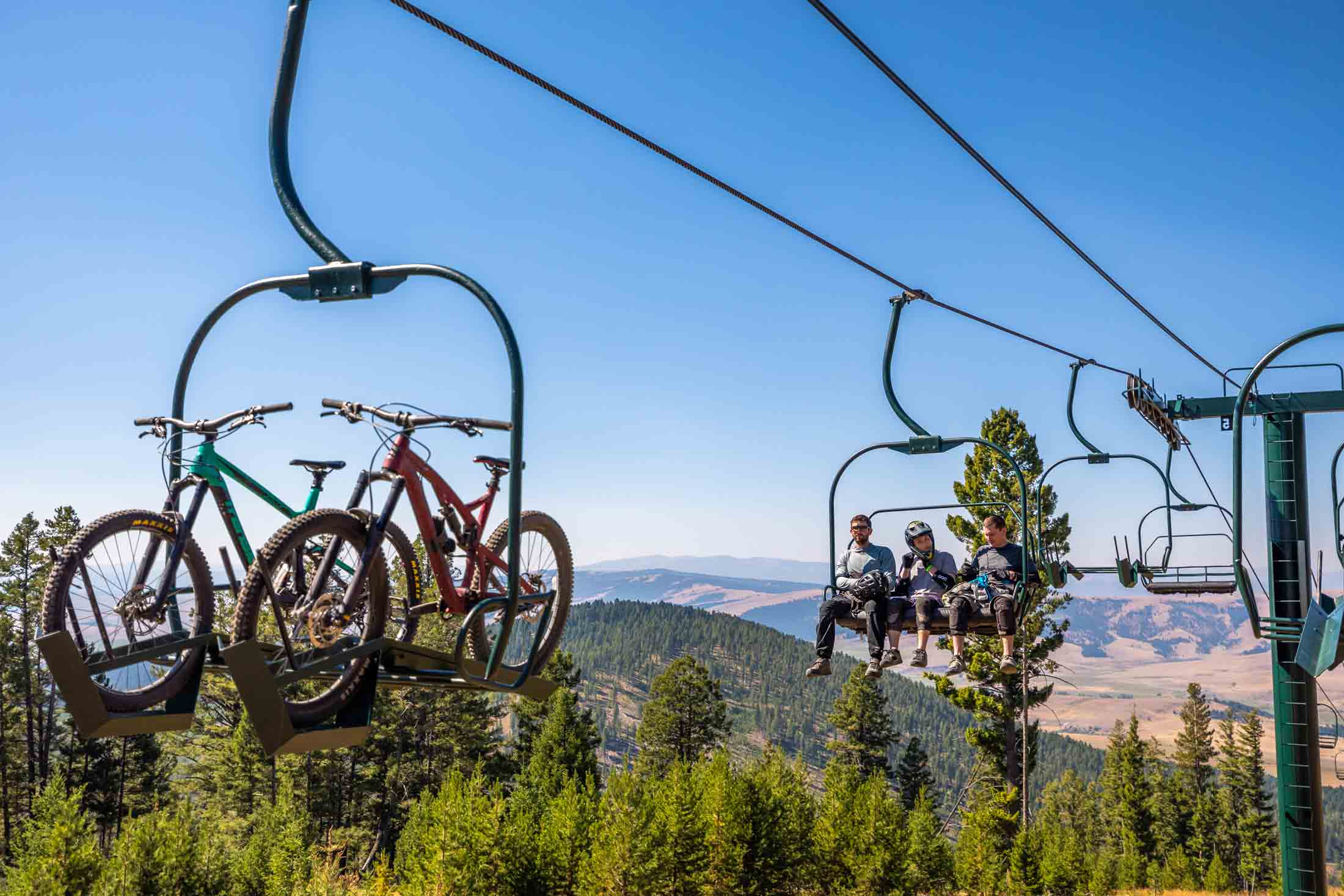 Cyclists on a lift with their mountain bikes at Discovery Bike Park in Philipsburg, Montana.